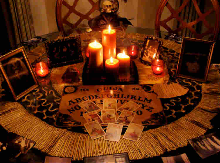 Ouija board setup with cards and candles